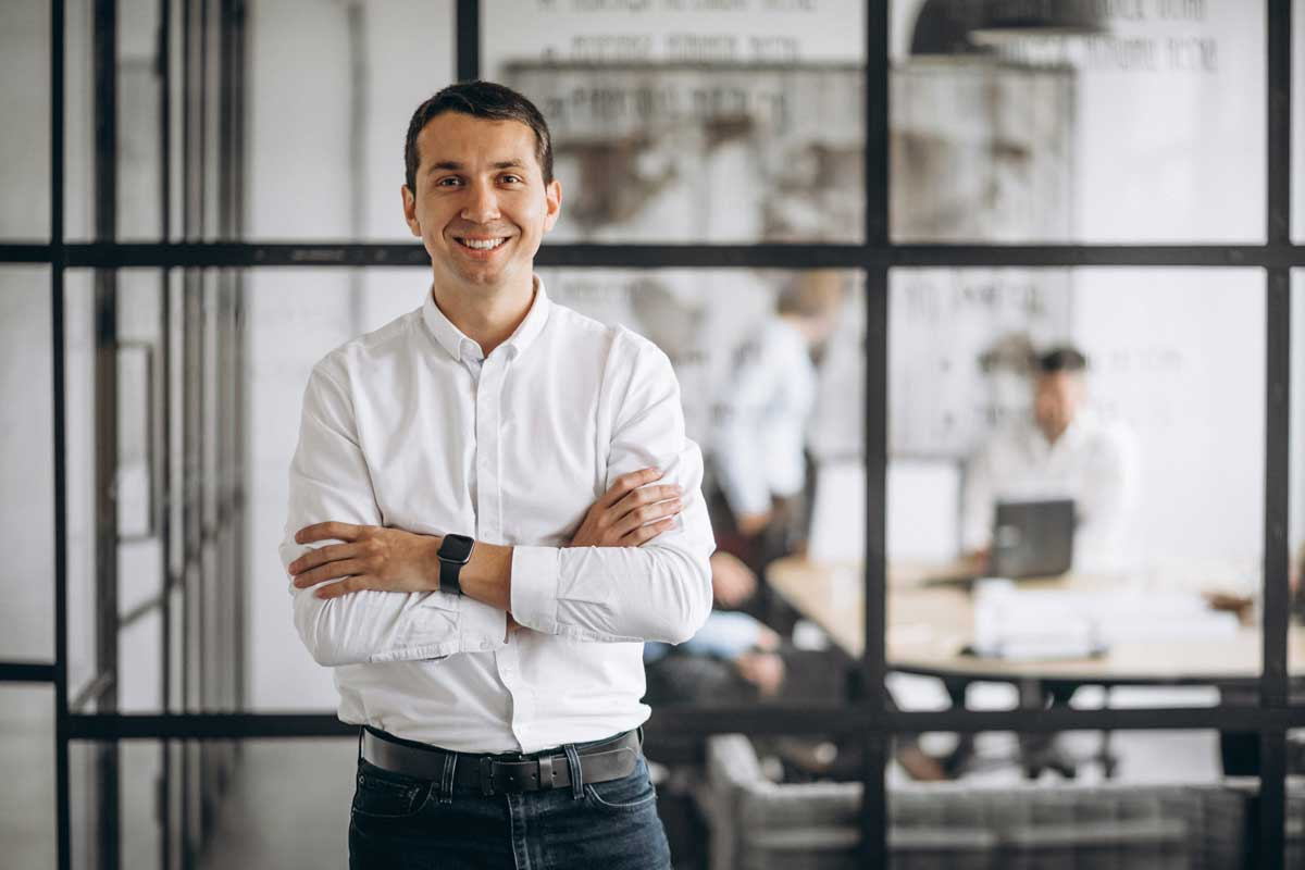 Man smiling at the camera whilst standing in a modern office