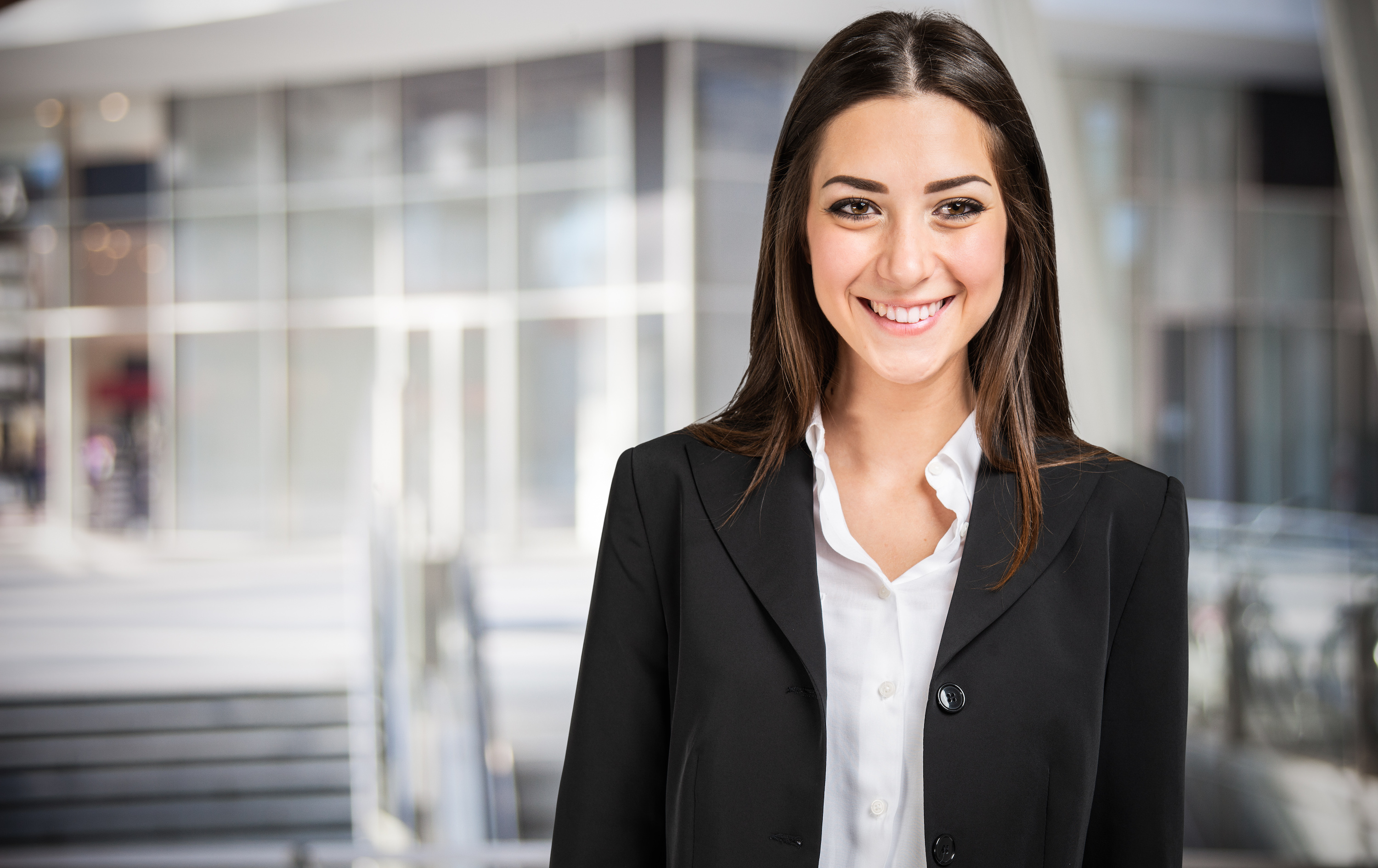 Young business woman in office environment looking at camera in black suit