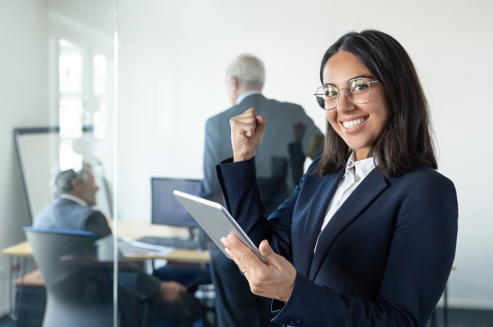 Businesswoman smiling at the camera in a happy pose in front of office