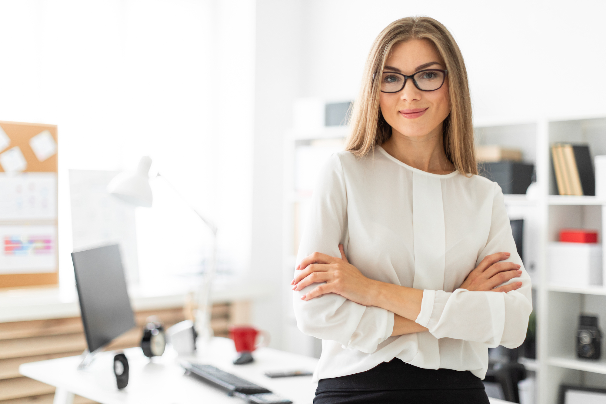 Professional woman standing in office with arms crossed
