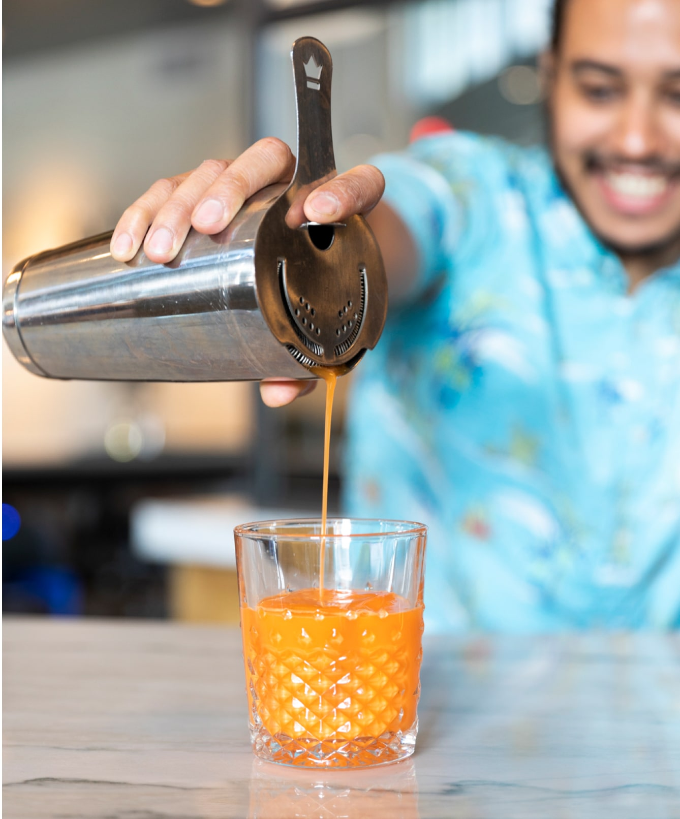 Bartender pouring an orange cocktail at the Atlanta Restaurant