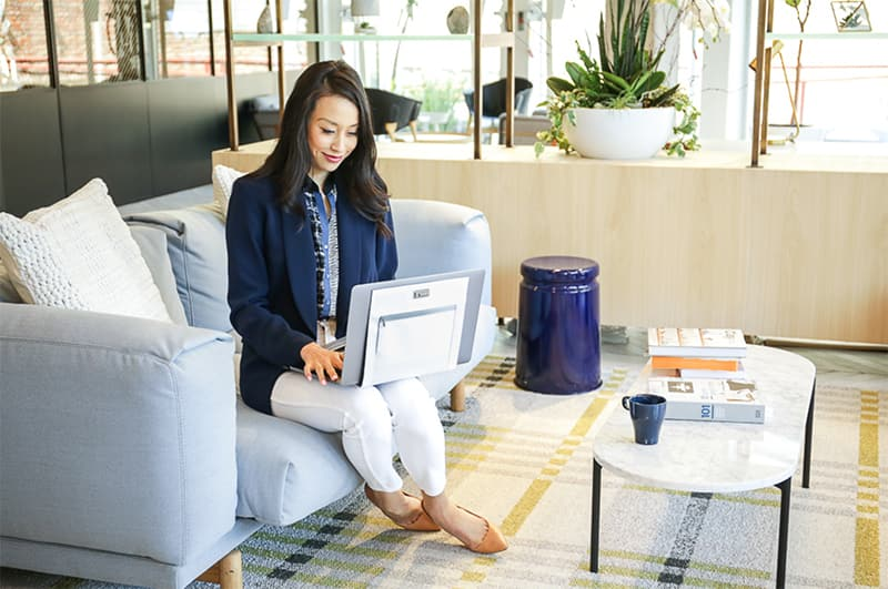 Asian woman using laptop in hotel lobby
