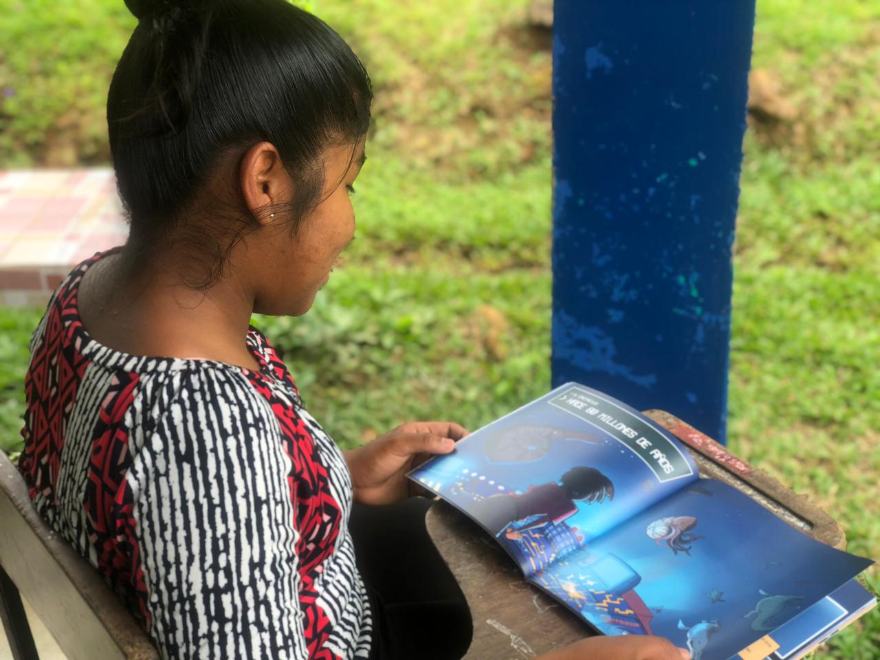 A young girl reading Martina and the Bridge of Time in school