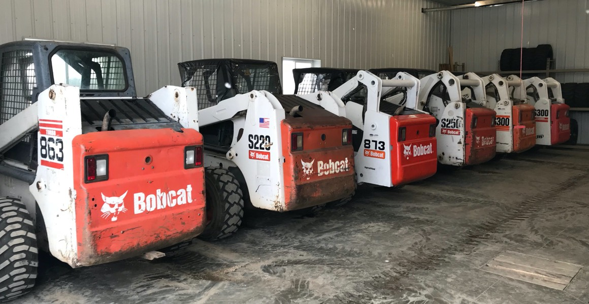 bobcat skid steers lined up in shop