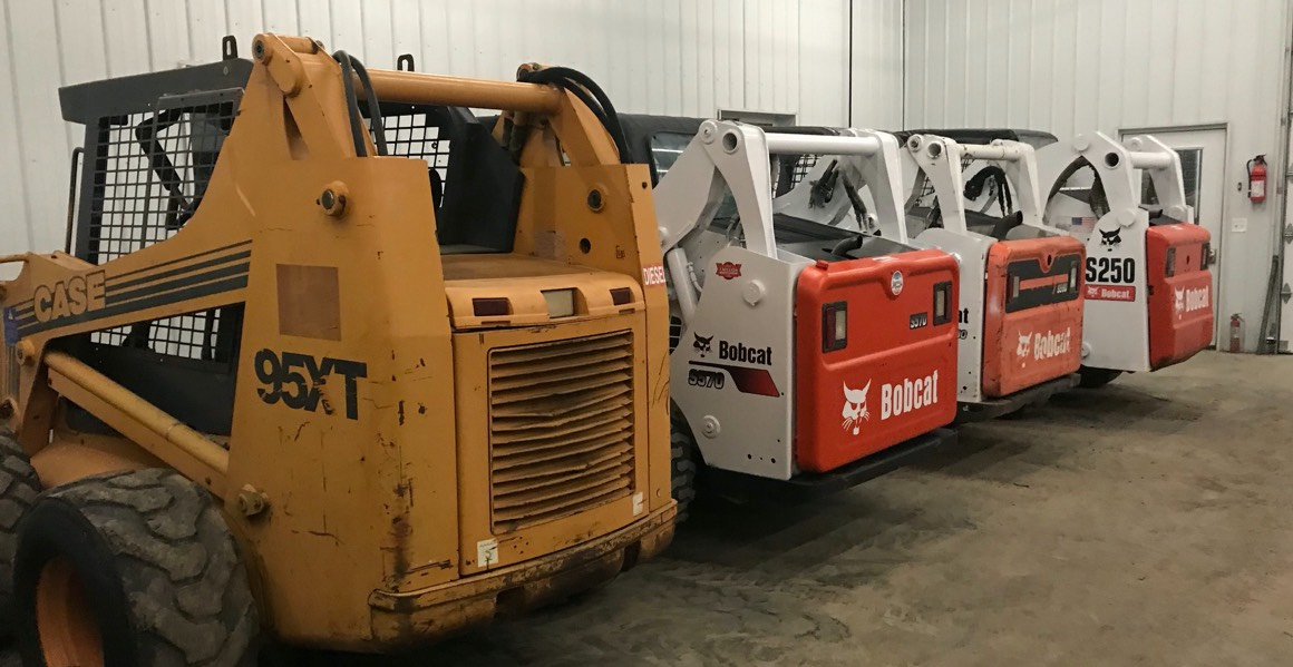 skid steers lined up in shop