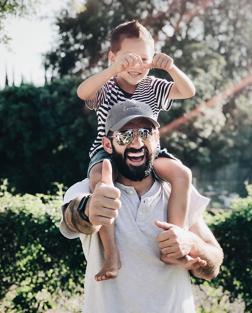 Fröhlicher Vater hält Kind auf Schultern und zeigt Daumen nach oben