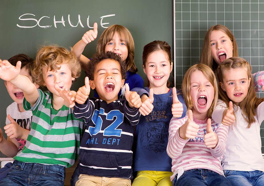 Grundschulkinder stehen freudig vor der Schultafel und strecken den Daumen nach oben