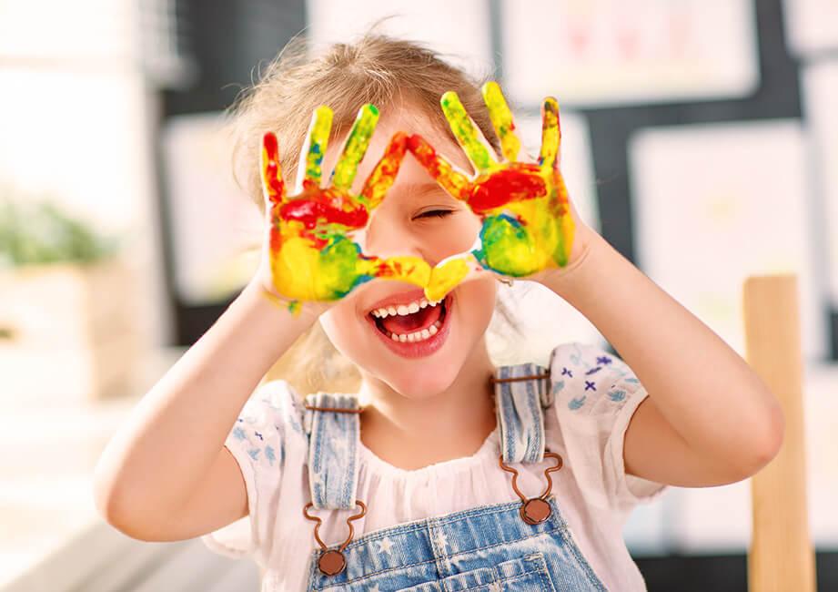 Ein Kindergartenkind zeigt seine bunt bemalten Hände