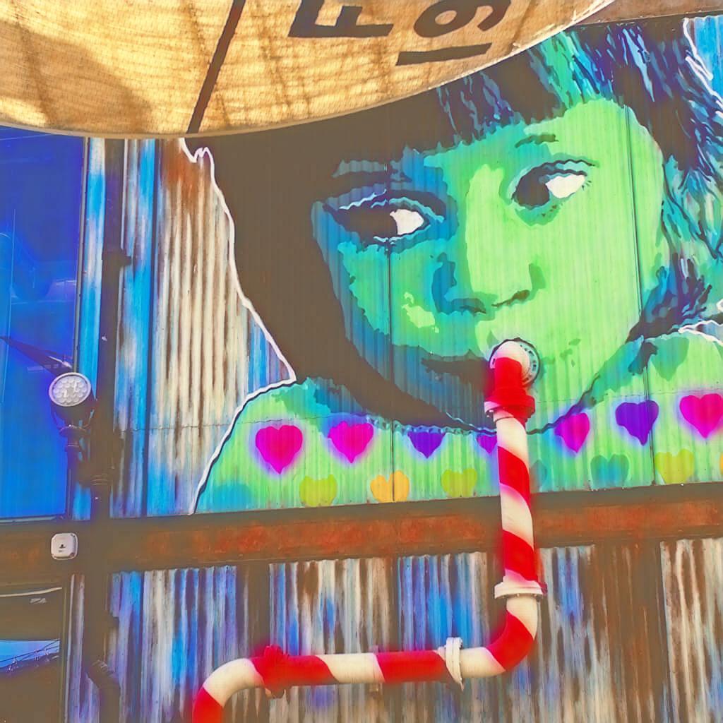 Streetart Kunstwerk, das ein Mädchen abbildet, welches aus einem Strohhalm trinkt