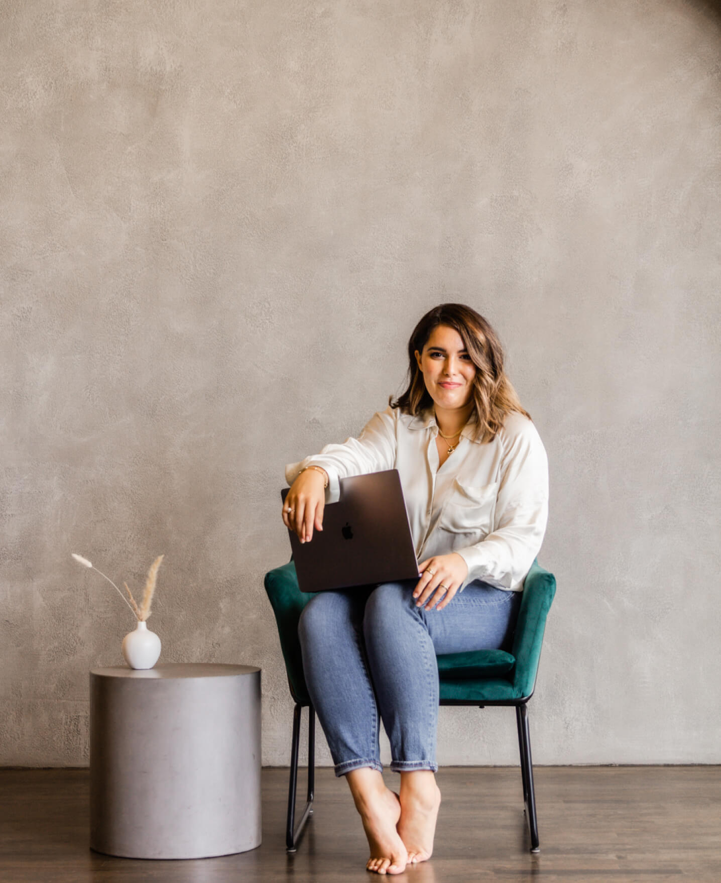 Lea, the Shopify designer and developer founder of Arq sitting on a green chair holding her laptop smiles at the camera