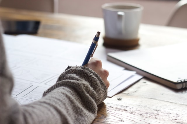 Schüler schreiben und Tasse