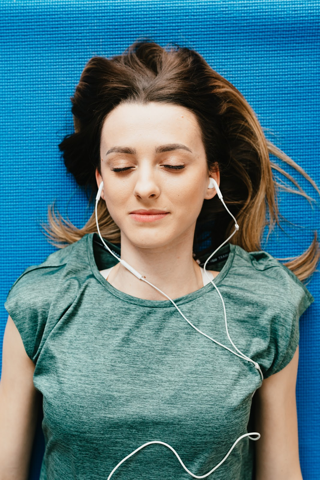 woman laying on mat with headphones in