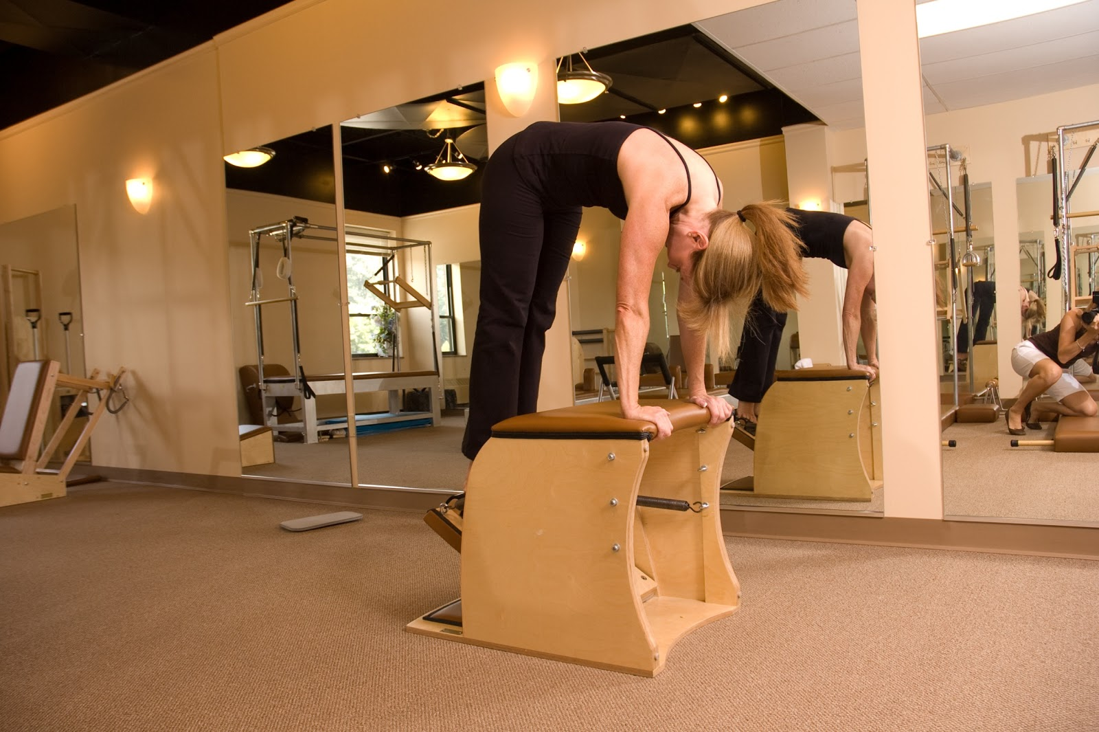 Owner of Touchstone Pilates, Lisa Pellow, stretches on equipment