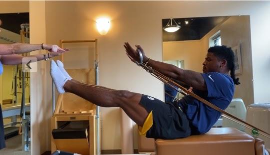 man stretching on pilates equipment