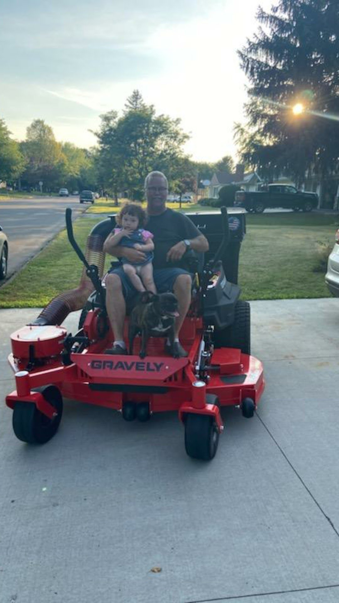 Image of Mark on lawnmower with his granddaughter.