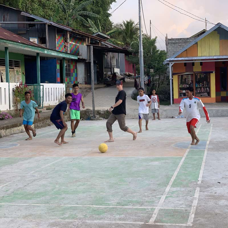 Go on your trip - a group of young men playing a casual game of soccer