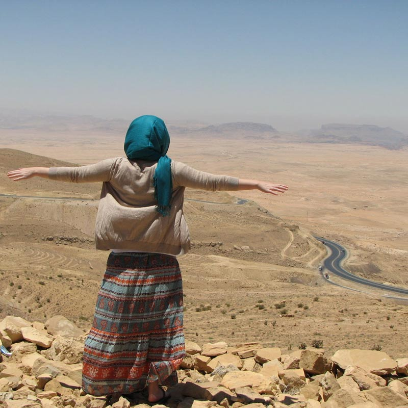 Go on your trip - Woman with headwrap looking down off a mountain
