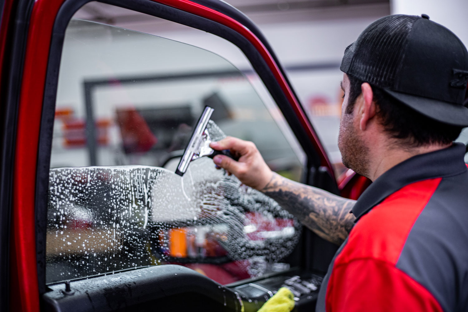 A man cleaning the car window after a tint installation.