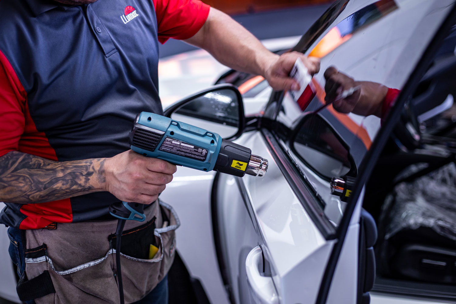 A man using heat to a prefect tint install.