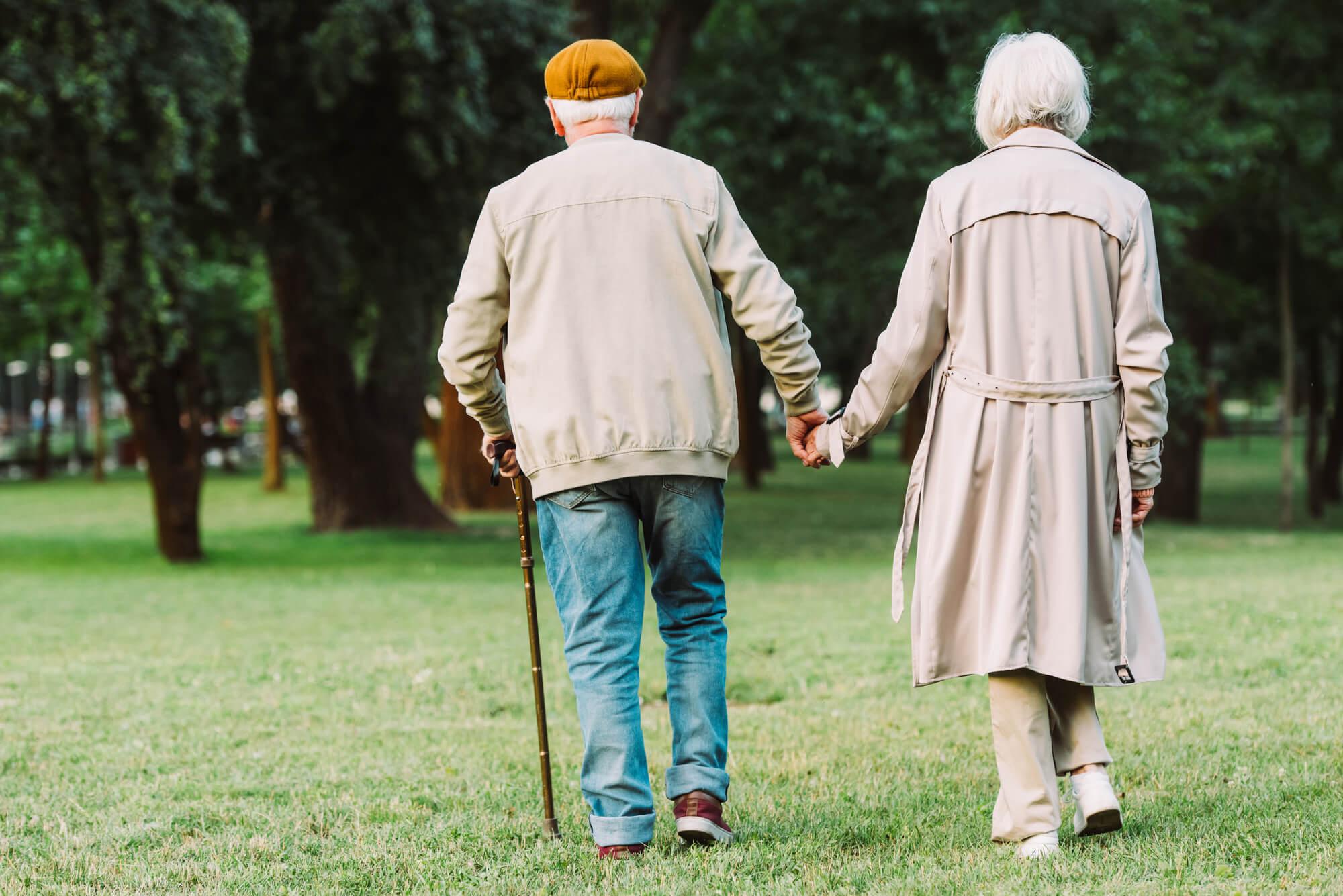 Elderly couple walking outside hand-in-hand at Memory Care in Geneva