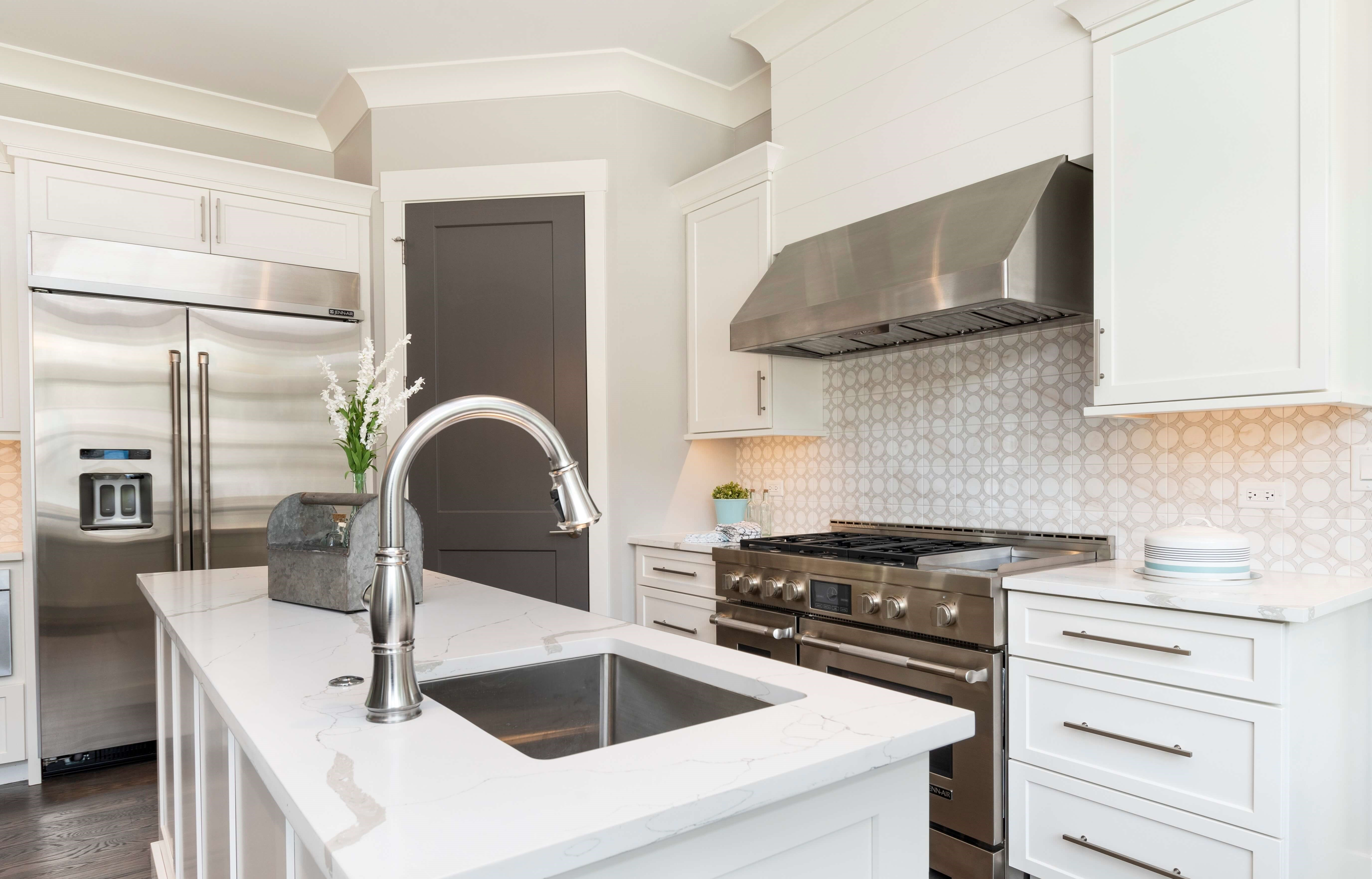 Beautiful kitchen with stainless steel appliances, white custom cabinets and backsplash