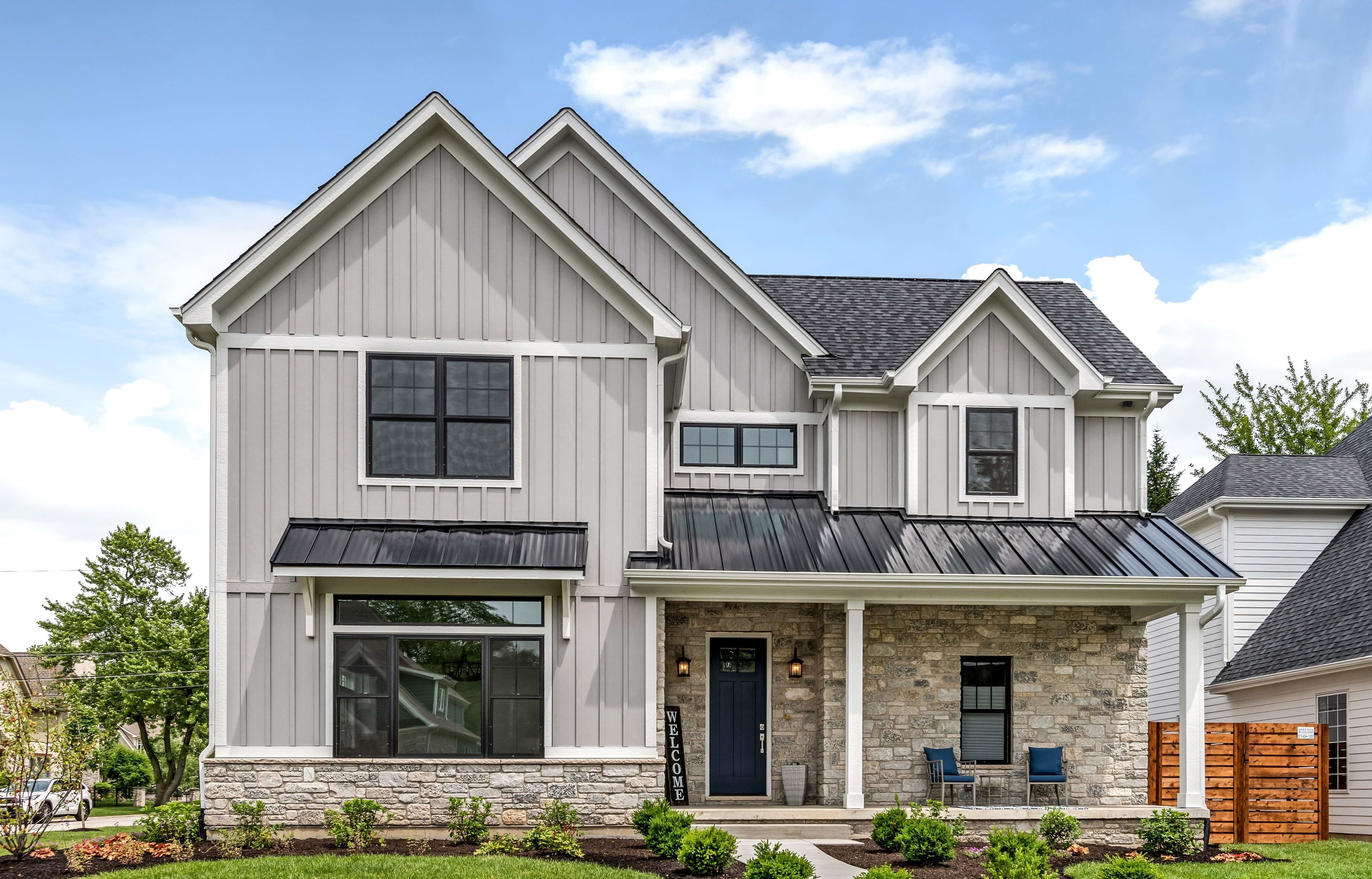Exterior farmhouse picture complete with windows, grey exterior, black roof and a dark blue door