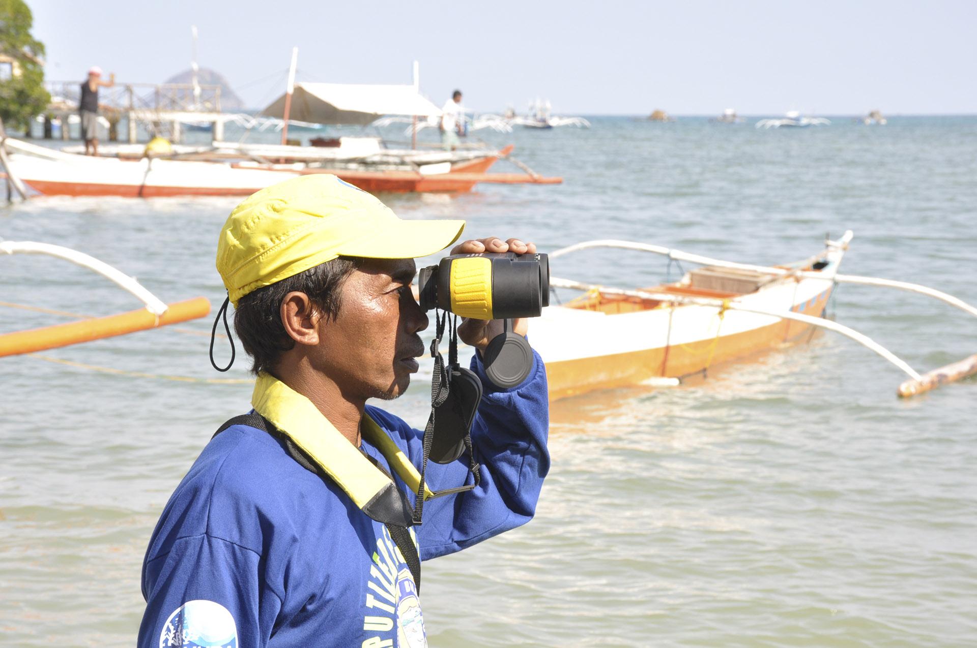 Man with binoculars near fishing boat at sea