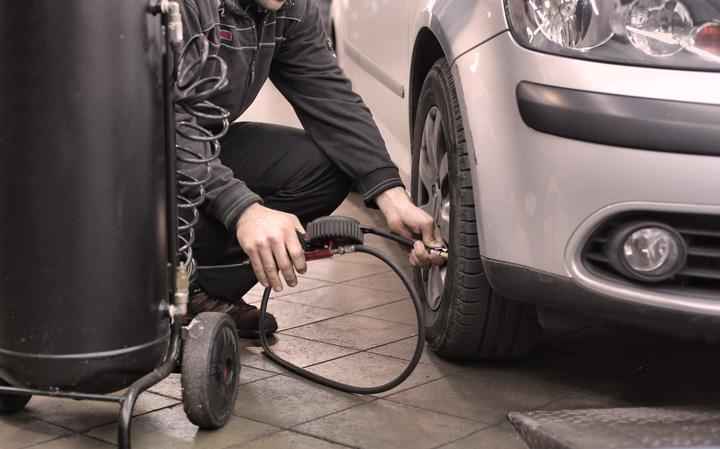 Mecânico com bomba de ar enchendo pneu de carro