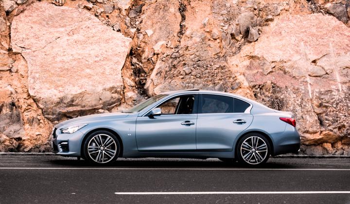 Sedã da Audi em rodovia ao lado de grande muro de pedras