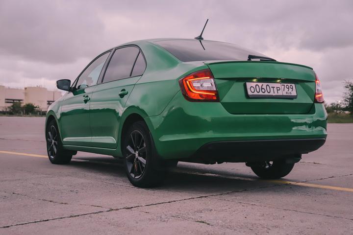 Carro sedã verde estacionado em pátio sob céu nublado