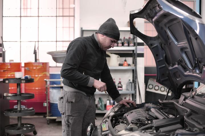 Mecânico em oficina verificando nível de óleo em carro com capô aberto