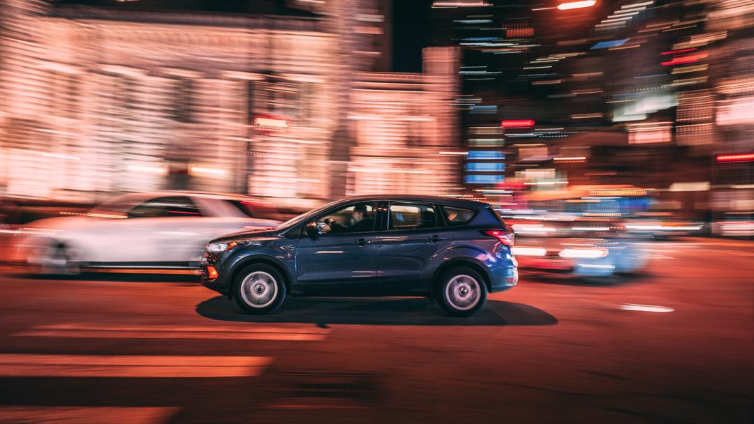 Carro SUV andando pela rua iluminada da cidade durante a noite