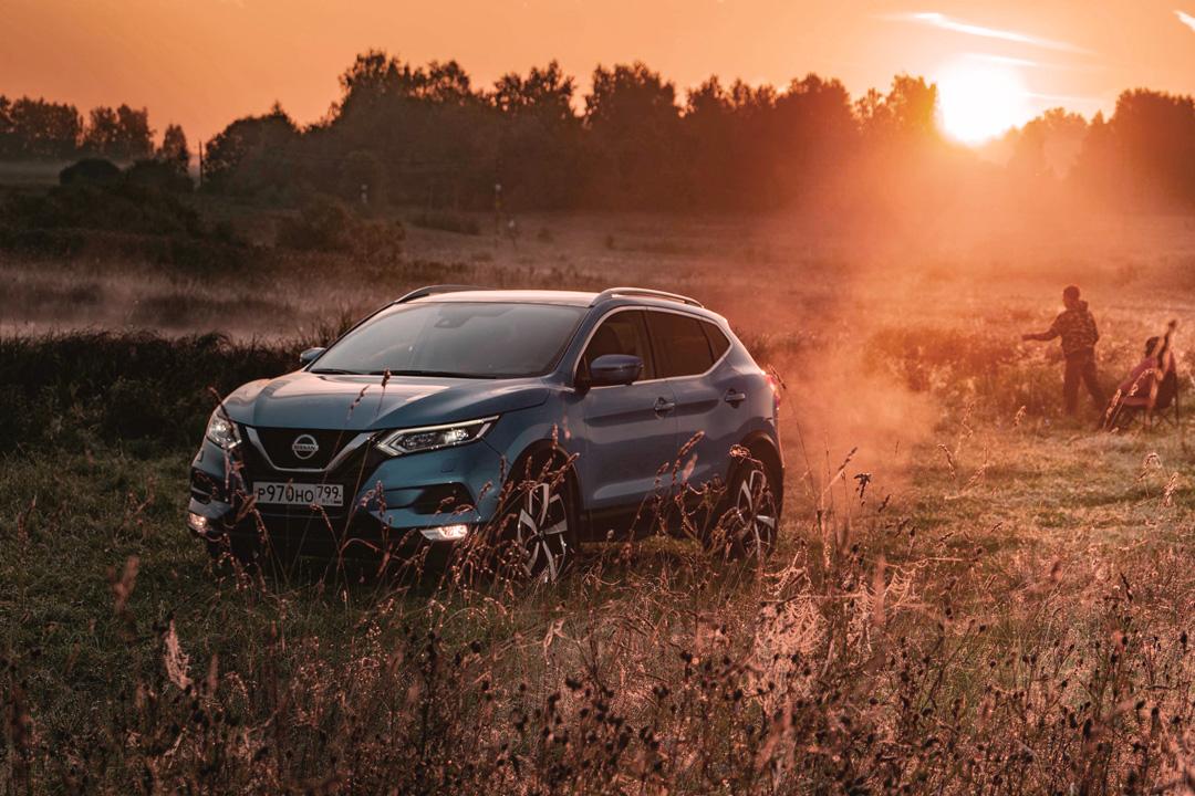 Carro SUV da Nissan andando no campo ao pôr do sol