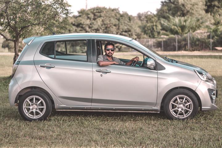 Homem apoiado em janela de carro hatch estacionado em gramado
