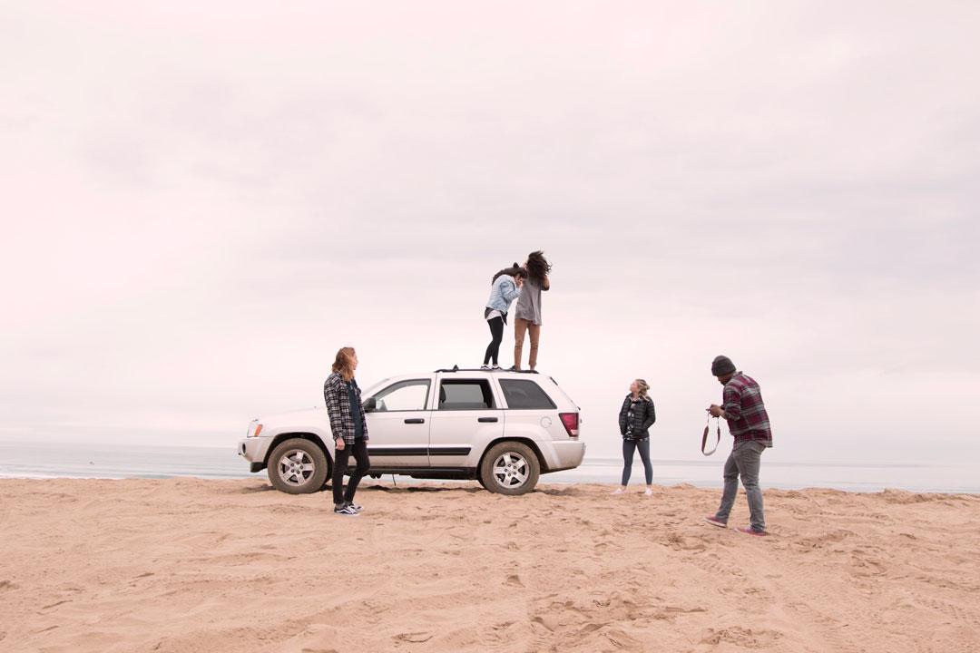 Jovens na praia se divertindo e subindo em cima de um carro SUV