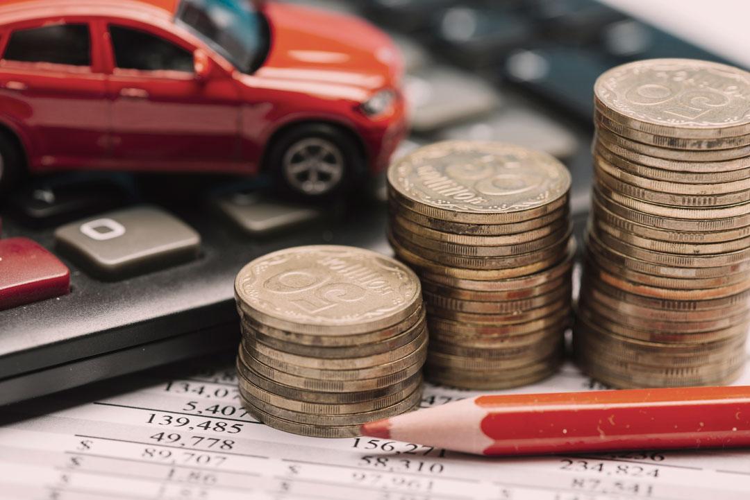 Planilha de cálculos, calculadora, lápis e moedas empilhadas junto a miniatura de carro