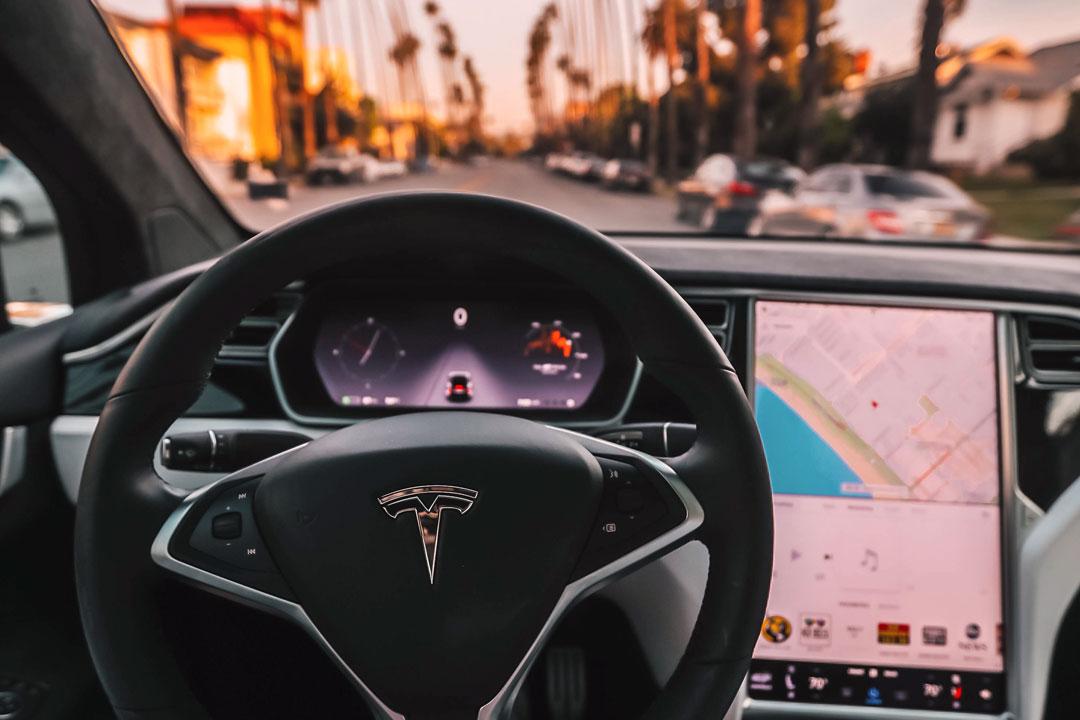Close interno de carro Tesla mostrando o volante e central do sistema Autopilot