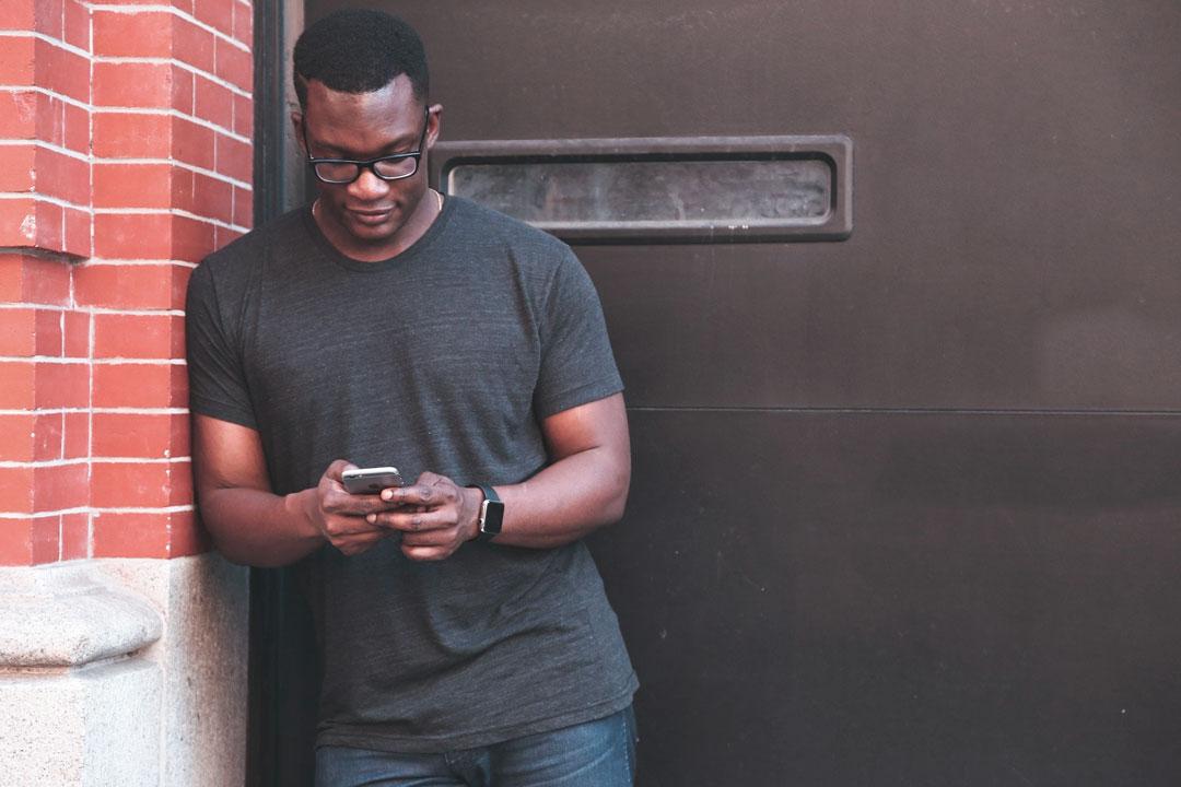Homem encostado em parede de tijolos fora de prédio acessando a Carupi em celular