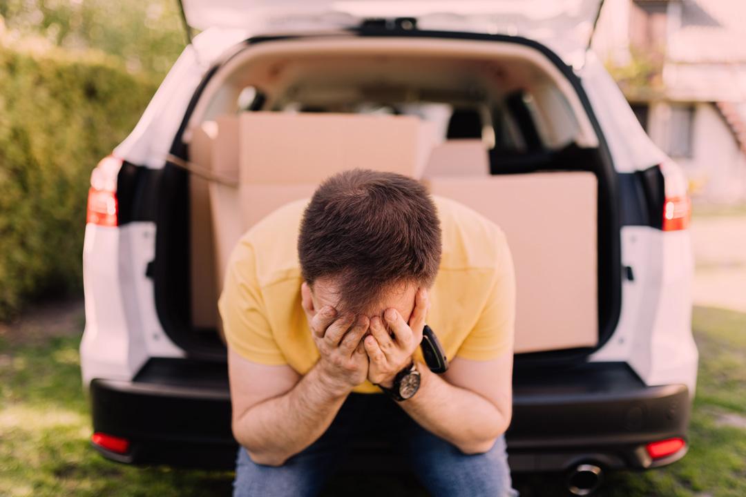 Homem triste sentado no porta-malas de seu carro