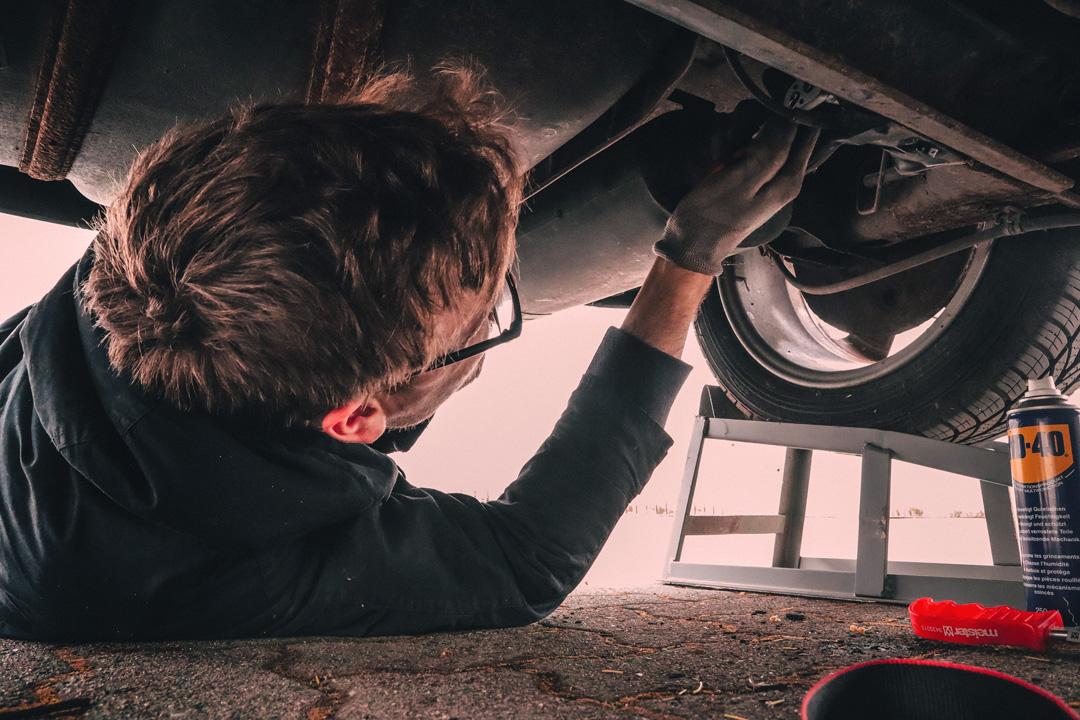Mecânico embaixo de carro realizando conserto no veículo