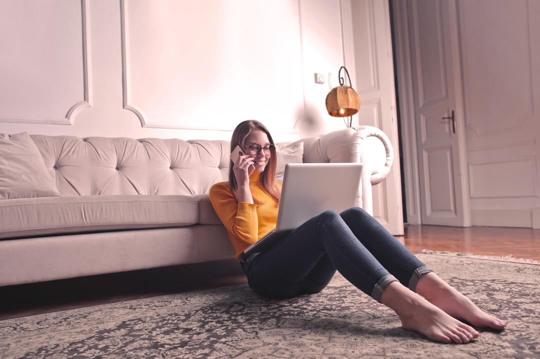 Jovem mulher sentada no sofá vendendo seu carro na internet com a Carupi