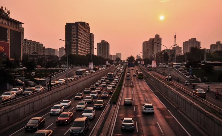 Entardecer em cidade grande com prédios e avenidas repletas de carros
