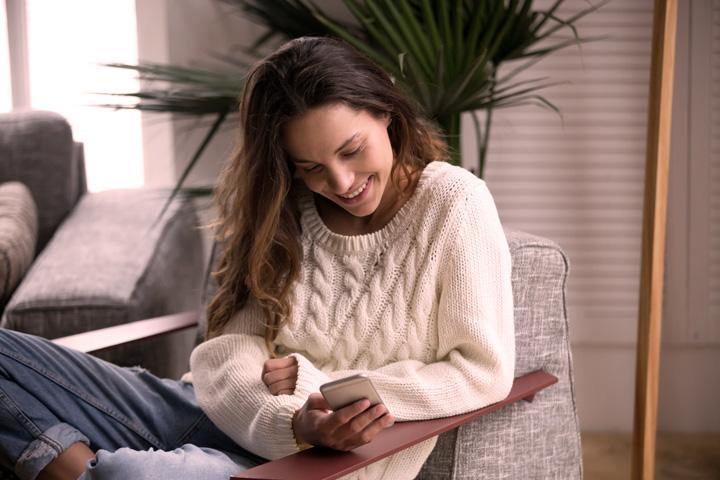 Mulher jovem em poltrona de sua casa acessando aplicativo da Carupi no celular