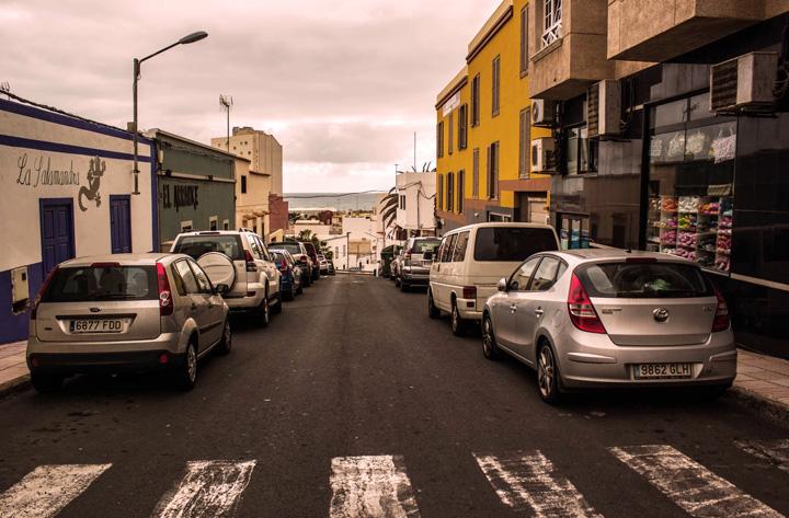 Rua central de cidade com diversos carros estacionados nos dois lados