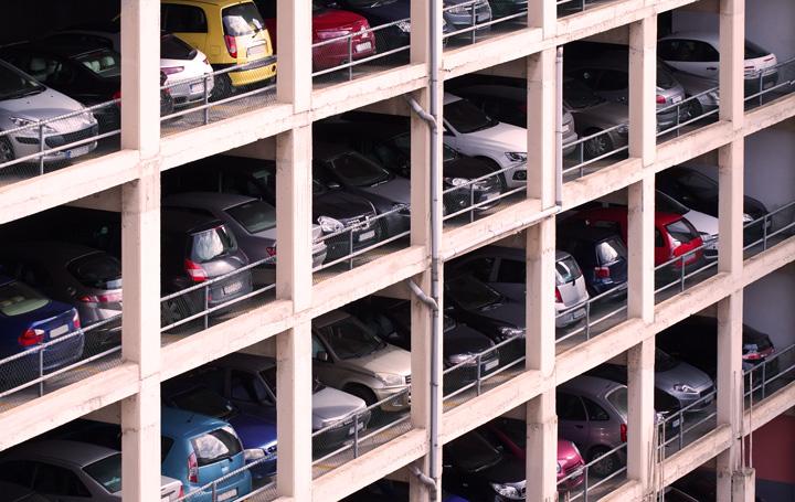 Prédio de estacionamento com vários andares repletos de carros nas vagas