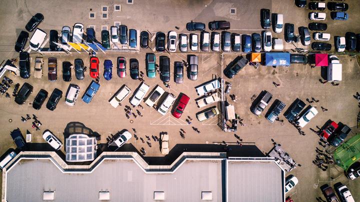 Visão aérea de estacionamento de shopping com muitos carros ocupando vagas ao ar livre