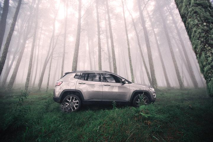 Jeep Compass em meio a floresta com raios de sol penetrando pelas copas das árvores
