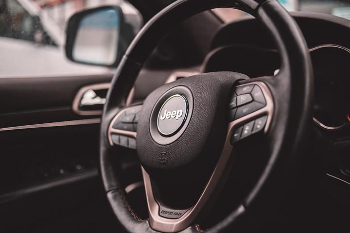 Close em volante de Jeep Renegade destacando símbolo da marca e controles do carro
