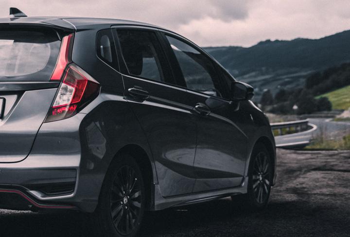 Visão traseira de Honda Fit parado em acostamento de rodovia