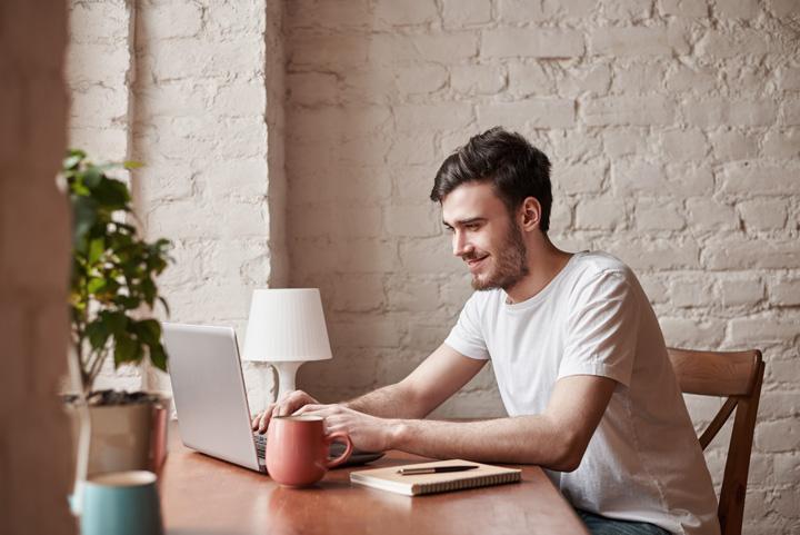 Rapaz sorridente em mesa de sua casa acessando plataforma Carupi em seu laptop